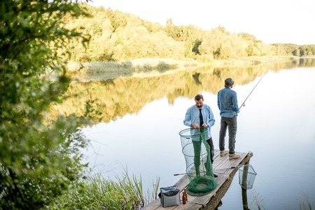 Two male friends preparing for fishing standing with fishing net and rod on the wooden pier during the morning light on the lake