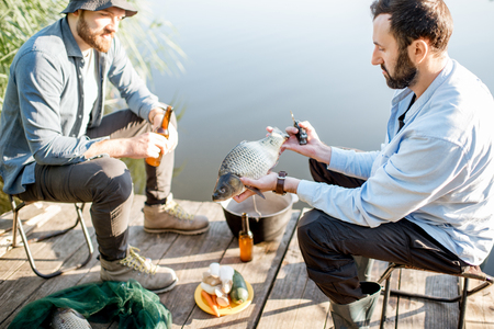Two friends sitting together with beer and fish on the picnic while fishing near the lake Zdjęcie Seryjne
