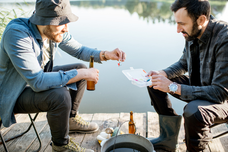 Two fishermen sitting together with fishing tackles sitting during the picnic near the lake