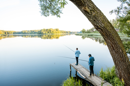 Landscape view on the beautiful lake with two male friends fishing together standing on the wooden pier during the morning light