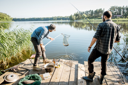 Two fishermen catching fish with fishing net on the lake in the morning Foto de archivo