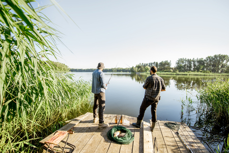 Landscape view on the beautiful lake and green reeds with two men fishing on the wooden pier during the morning light Banque d'images - 104716454