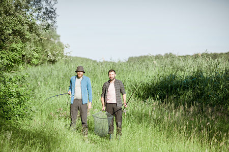 Two fishermen walking with fishing rod and net on the green lawn near the lake in the morning