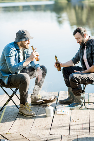 Two fishermen frying fish sitting with beer during the picnic on the wooden pier near the lake in the morning