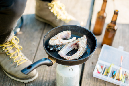 Frying two fish steakes on the burner during the picnic with beer and fishing tackles outdoors 写真素材 - 104716464