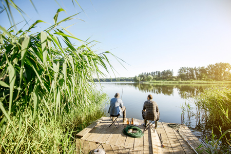 Landscape view on the beautiful lake and green reeds with two men fishing on the wooden pier during the morning light Banque d'images - 104716495