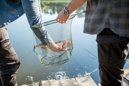 Fisherman getting caught fish from the fishing net near the lake in the morning Stock Photo