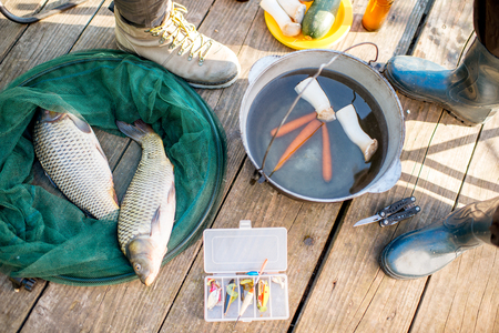 Fishermens picnic with fish, soup and fishing tackles on the wooden pier