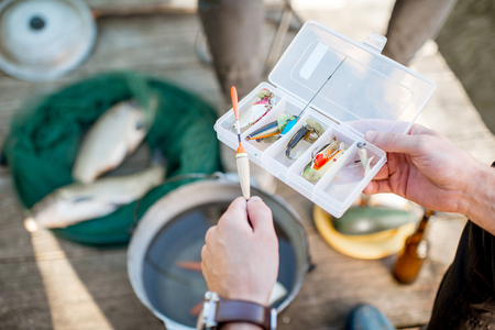 Fisherman holding box with fishing tackles during the picnic outdoors, close-up view Stock Photo