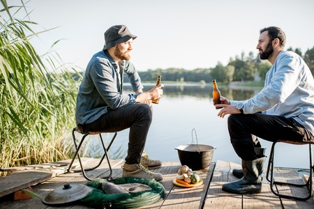 Two male friends relaxing with beer sitting together during the fishing process on the pier near the lake