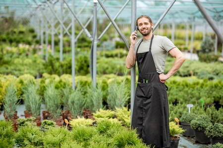 Handsome gardener talking with phone during the work in the greenhouse of the plant shop