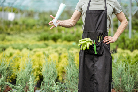 Tools for gardening in the pocket of working apron of the male worker in the greenhouse 版權商用圖片