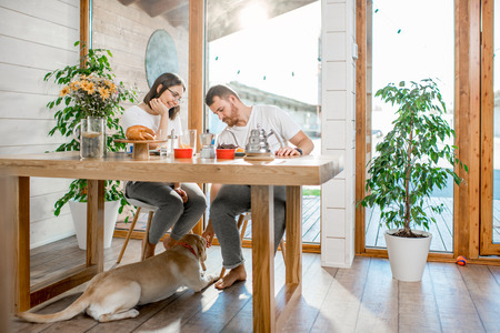 Young couple having a breakfast sitting at the table with their dog in the wooden country house