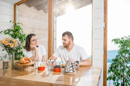 Young lovely couple in white t-shirts having a breakfast sitting at the table in the wooden house