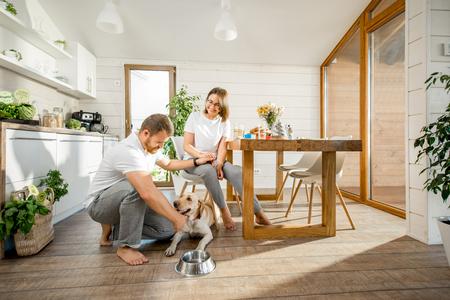 Jeune couple jouant avec un chien pendant un petit-déjeuner dans la salle à manger de leur belle maison de campagne en bois