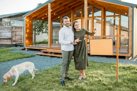Elegant and happy couple standing in front of their new and beautiful wooden country house with empty plate to copy space