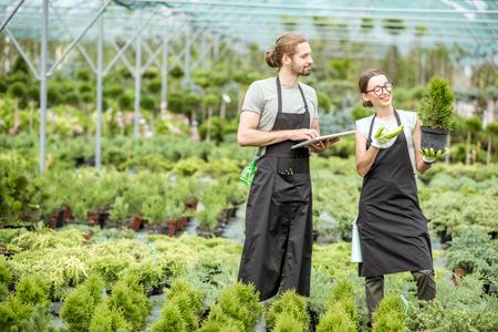 Paar Arbeiter in Uniform mit digitalem Tablet, die sich um Pflanzen im Gewächshaus des Pflanzenladens kümmern