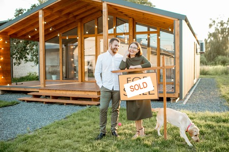 Elegant and happy couple standing in front of their new and beautiful wooden country house