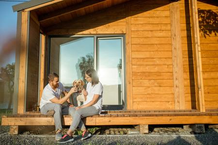 Junges reizendes Paar, das mit Hund auf der Terrasse auf dem Hinterhof ihres hölzernen Landhauses sitzt