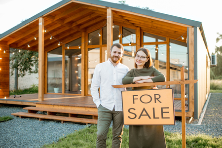 Elegant couple standing near the beautiful wooden country house for sale Stockfoto