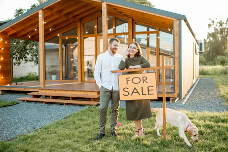 Elegant couple standing with dog near the beautiful wooden country house for sale