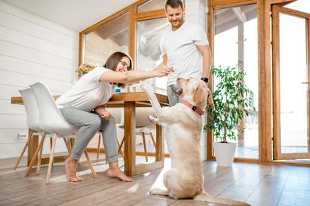 Giovani coppie che giocano con il cane durante una colazione nella sala da pranzo della loro bella casa di campagna in legno