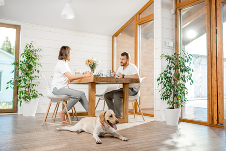 Young couple having a breakfast sitting with dog in the dining room in the wooden country house Stock Photo
