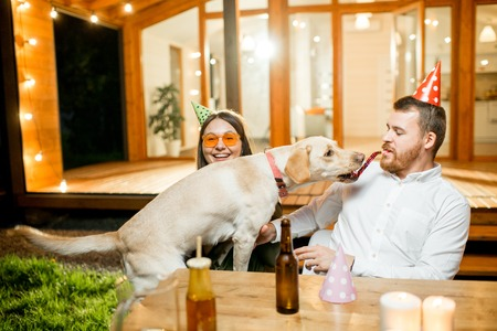 Funny dog with young couple sitting at the table during a celebration on the backyard of the house outdoors