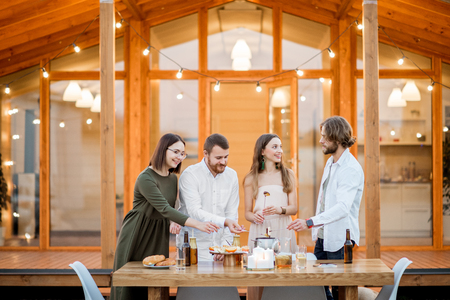 Four friends enjoying evening time having a dinner on the backyard of the modern country house outdoors