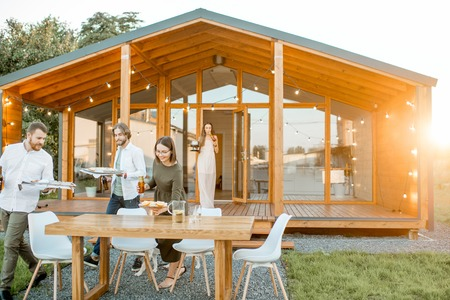 Amigos felices llevando comida preparándose para la cena en el patio trasero de la moderna casa de madera durante la puesta de sol