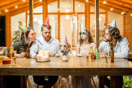 Friends celebrating dogs birthday with cake at the table on the backyard of the house in the evening Stockfoto