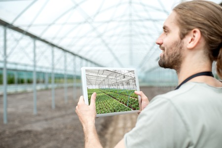 Farmer holding digital tablet with project of the future plantation in the glasshouse 写真素材 - 105233957