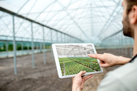 Farmer holding digital tablet with project of the future plantation in the glasshouse