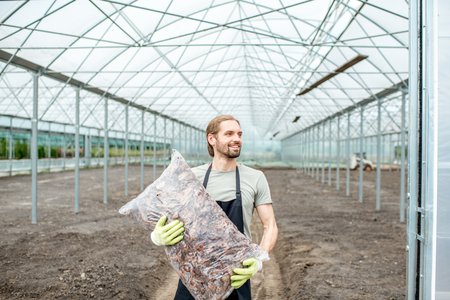 Portrait of a handsome farmer in working uniform carrying bag with bark for mulching in the glasshouse