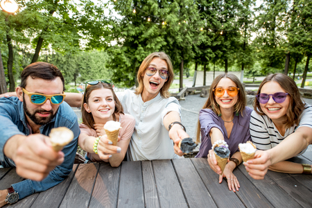 Young friends having fun with ice cream sitting together outdoors in the park Imagens
