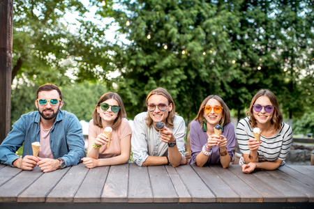 Portrait of a young friends sitting together with ice cream outdoors in the park Imagens