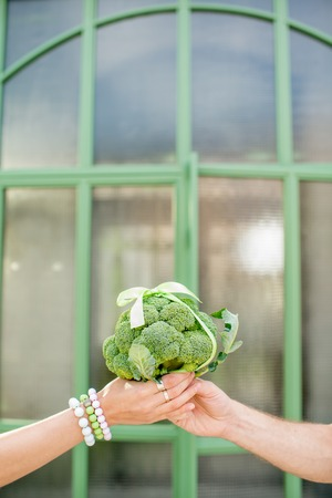 Giving fresh bunch of broccoli tied in a bow as a gift outdoors on the green background, close-up view Reklamní fotografie