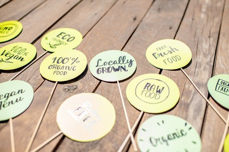 Green stickers with healthy food slogans on the wooden table