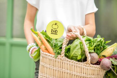 Zak vol verse biologische groenten houden met groene sticker van de lokale markt op de groene achtergrond Stockfoto