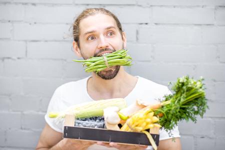 Porträt eines gutaussehenden Mannes, der grüne Bohnen beißt, die mit Kasten voll frischem Gemüse auf dem Backsteinmauerhintergrund stehen