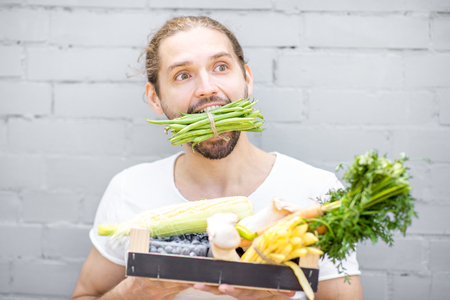 Portrait of a handsome man biting green beans standing with box full of fresh vegetables on the brick wall background Stock Photo