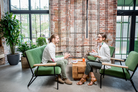 Business people sitting on the green sofas during a lunch at the beautiful loft interior on the brick wall background