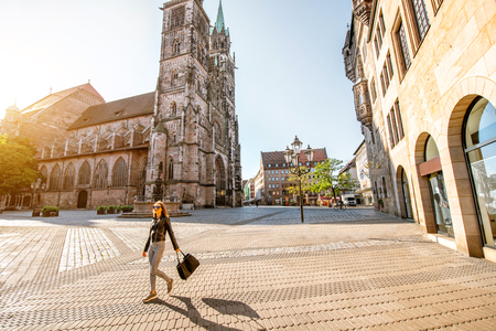 Morning view on the saint Lorenz cathedral with woman walking in the old town of Nurnberg, Germany