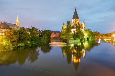 View on the riverside with illuminated Neuf basilica during the twilight in Metz city in France