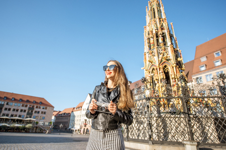 Young woman tourist near the beautiful fountain on the market square traveling in Nurnberg, Germany