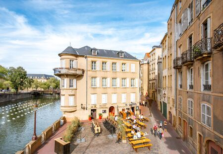 METZ, FRANCE - August 26, 2017: View on the riverside with beautiful old buildings and cafes in Metz city in Lorraine region of France