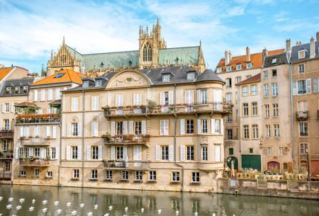 METZ, FRANCE - August 26, 2017: View on the riverside with beautiful old buildings, cathedral on the background and paper boats on the water in Metz city in Lorraine region of France