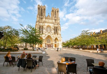 REIMS, FRANCE - August 27, 2017: View on the square with cafe bar near the famous Notre-Dame cathedral in Reims city, France Sajtókép