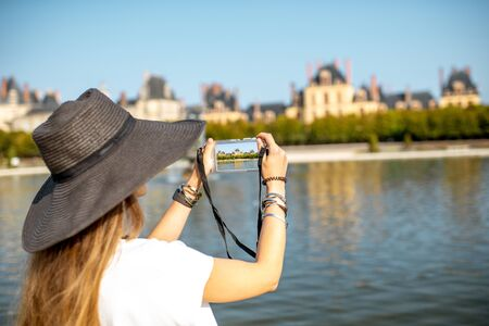 FONTAINBLEAU, FRANCE - August 28, 2017: Young woman tourist photographing with photocamera Fontainebleau palace, France