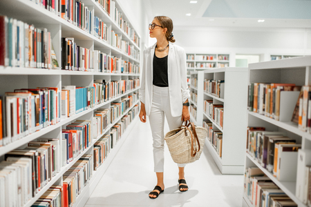 Young woman searching books walking at the modern library interior with white bookshelves Stock Photo